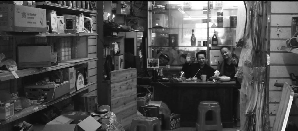 Black and white image of two men sitting inside a shop cluttered with objects, both are smiling and waving to camera.