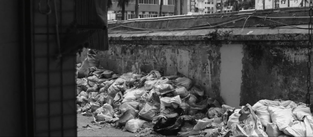 Black and white image of side street with bags of rubble lined up along the side