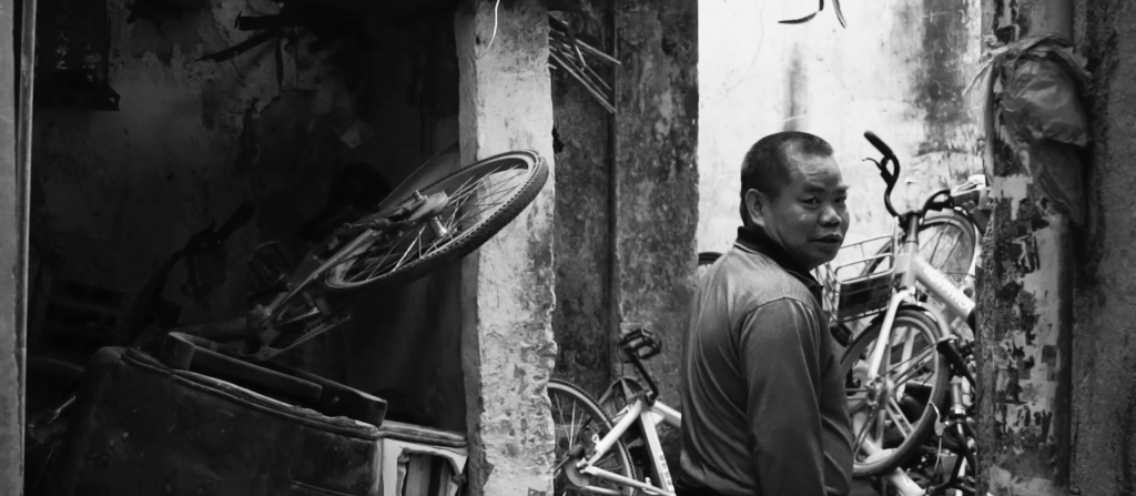 black and white image of a man in an alleyway, turning to look over his shoulder towards the camera. In front of him are many 'pay to use' bikes piled up high.