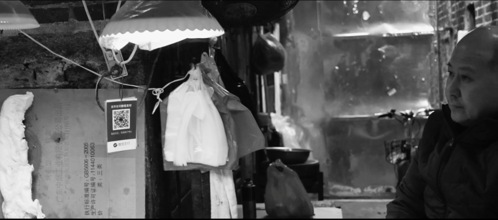 Black and white image of man looks to the right, at his outdoor butchers stall. Low level hanging lights and plastic bags are in the frame. He is wearing a warm coat suggesting that it is a cold day.