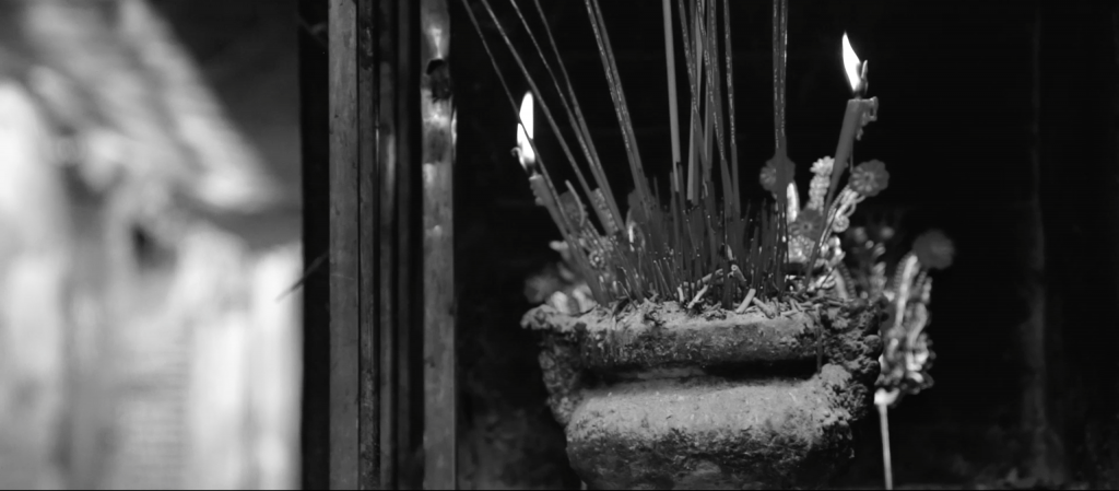 Black and white image of a incense holder in an Chinese shrine, filled with candles, incense and ash