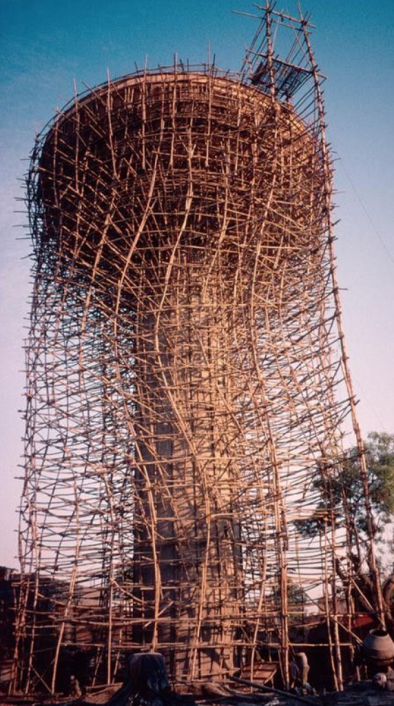 Image of a mushroom-shaped structure. The structure is higher than the trees. On the structure, all around it, is a fine scaffold made of sticks or poles of wood. The scaffold twists at points and looks like a protective barrier around the structure.