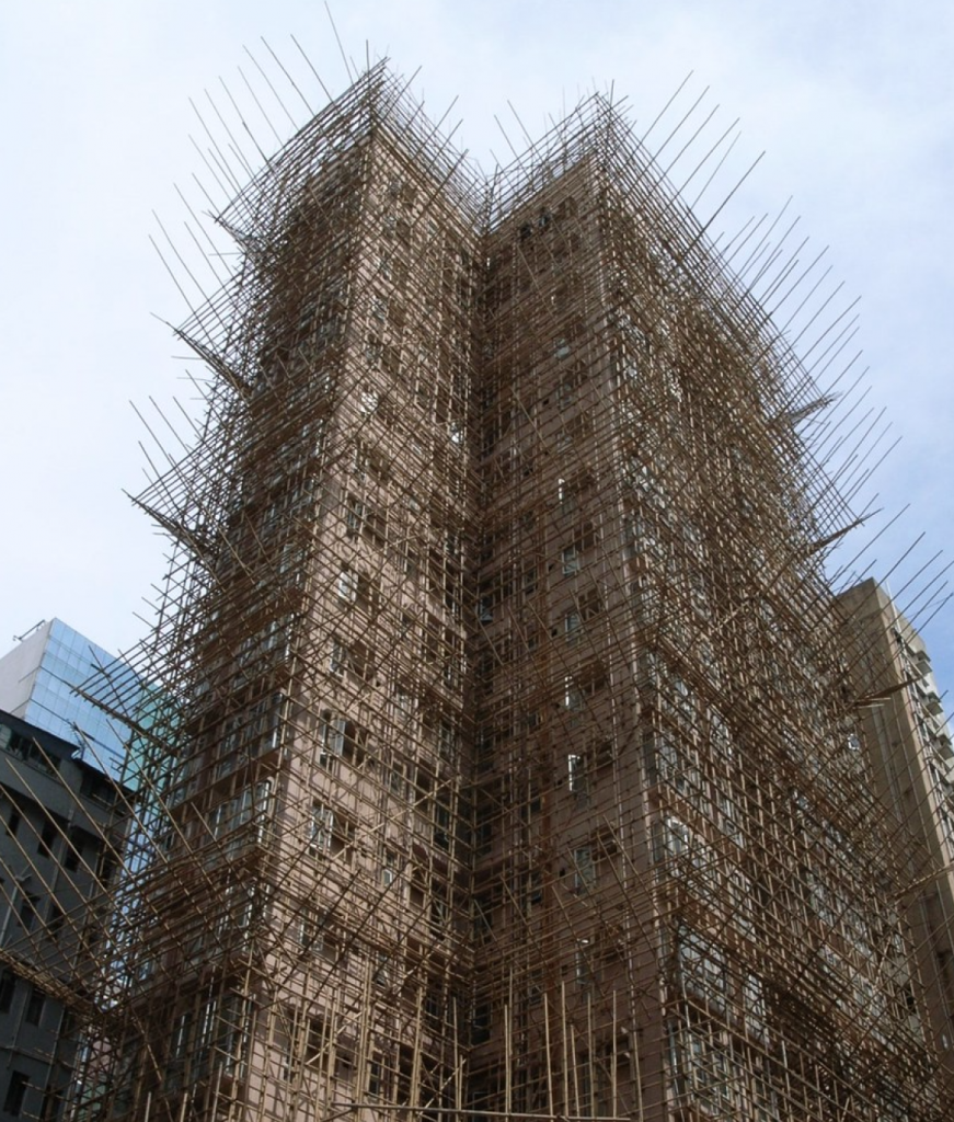 A building with a very fine-looking scaffold that completely covers every seen facade. The scaffold looks as though it's made completely of thin metal poles and nothing else.