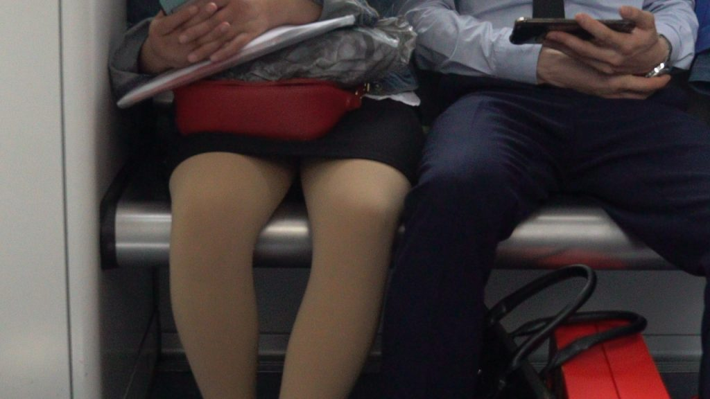 A man and a woman sit next to each other in the metro. The woman wears restaurant worker clothes ( a skirt and shirt. with a red handbag) and the man wears business attire (a shirt and trousers with a red package on the floor.)