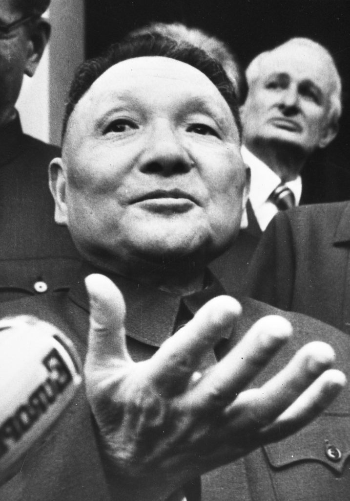 Black and white image of Deng Xiaoping in mid-speech, raising his right hand as he addresses and audience in Paris (1976)