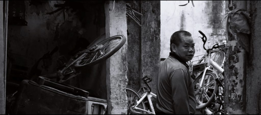 Black and white photograph, with a man to the right of the image, looking out at the viewer from the photo. Several (what appear to be) abandoned bicycles are piled on the corners to the left and right of the image.