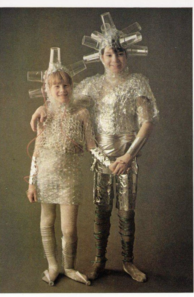 Two kids wearing space suits made out of plastic cups and bubble wrap.