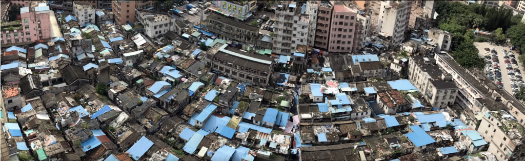 Birds eye view of a low-rise settlement, with roofs coloured blue, or with old stone or corrugated steel.