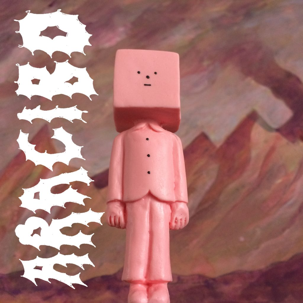 Colour photo of a pink plastic figure. The figure has a cube shaped head. It is photographed from a worms eye view. the background is of a mountain range, it is painted in pink, red, and purple watercolour paints. On the righthand side of the image the word 'Aracibo' is written in spiky, white block letters.