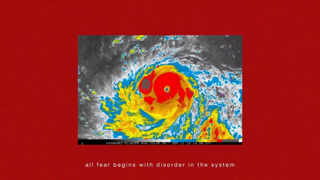 A thermal aerial image of a hurricane swirling in bright red, yellow, blue and black & white is shown in a rectangle, framed by a blood red background. On the bottom of the image white text reads: 'all fear begins with disorder in the system'.