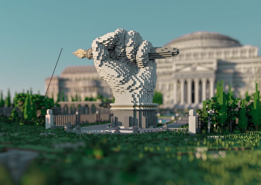 An image from The Uncensored Library project. This is a view of the front entrance of the virtual library in Minecraft. A virtual sculpture of a raised fist holding a dip pen in a garden with trees and grass is in the foreground. The library itself is slightly of focus in the background in order to emphasize the sculpture. The library is built using a neoclassical architectural style with big columns and a domed rooftop. It is intended to resemble well-established institutions such as the New York Public Library, as well as stylistically allude to the authoritarian structures the project aims to subvert.