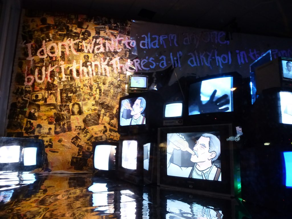 """Installation view of an exhibition. On the left of the image is a tree-shaped collage of many, many black and white images (it's not very clear as the images are small, but some are portraits of people) - they are lit in a sunshine yellow light. The floor of what is assumed to be a gallery is chrome, and reflects the rest of the room. 12 TV monitors make a wall on the right of the image, on 2 screens are an animation of a man drinking from a bottle, on another is a hand touching the screen, other screens are whited out or unclear. On a On the wall and written over the photos in large handwriting is written: I don't want to alarm anyone but I think there's a lil alkyhol in the..."""" unreadable from there."""