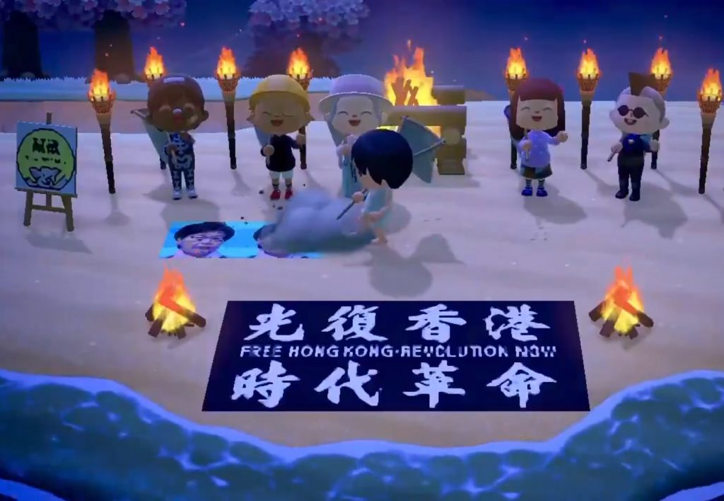 Burning torches and a protest banner, that reads 'Free Hong Kong, Revolution Now', on a beach in Animal Crossing. Gamers are free to whack the portrait of Carrie Lam, Chief Executive of Hong Kong on the beach. There are 5 characters in the background cheering for another character who is destroying a portrait of Lam. On the left, here is also a small painting on an easel with the image of a piggy (one of the mascots of Hong Kong protest).
