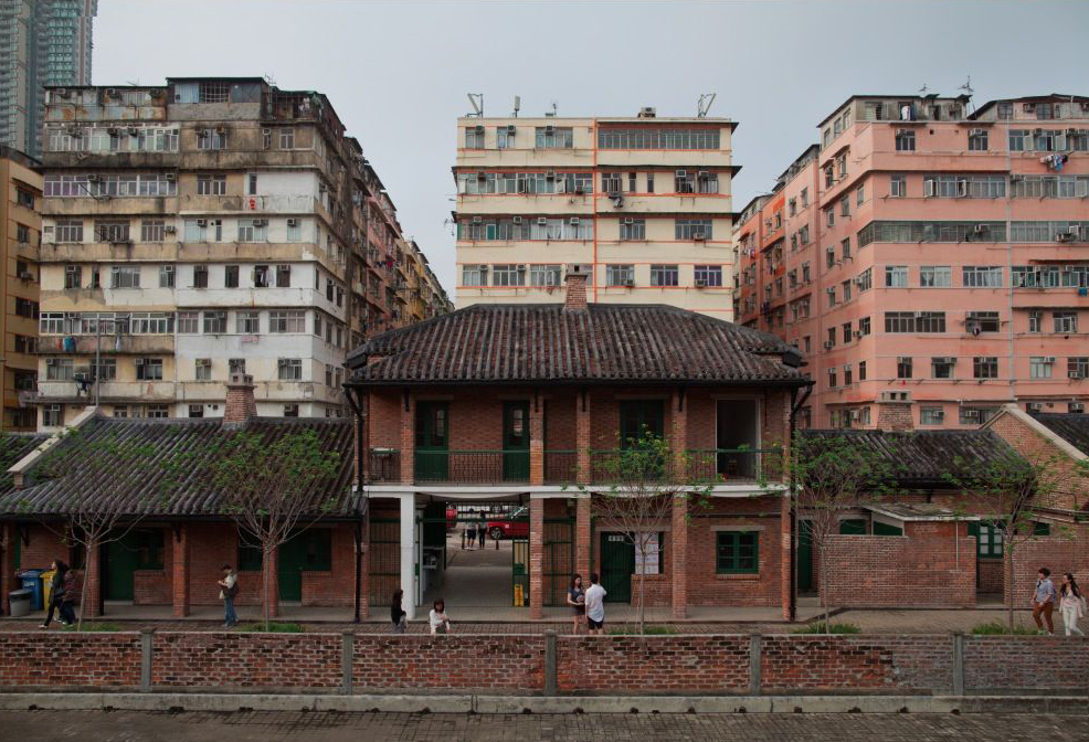 Photograph showing the entrance to Cattle Depot in Hong Kong. The entrance is an archway inside a red brick building on two storeys, with two smaller outbuildings either side. The roofs of the buildings are covered in a dark rough tile, which is in parts covered in a red moss. Behind the buildings are tenement buildings, each approximately 10 storeys high; the one on the left is pale blue and grey, the central one is cream with orange stripes running beneath the windows, and the one on the right is pale salmon-orange/pink. The sky is overcast, pale grey-blue.