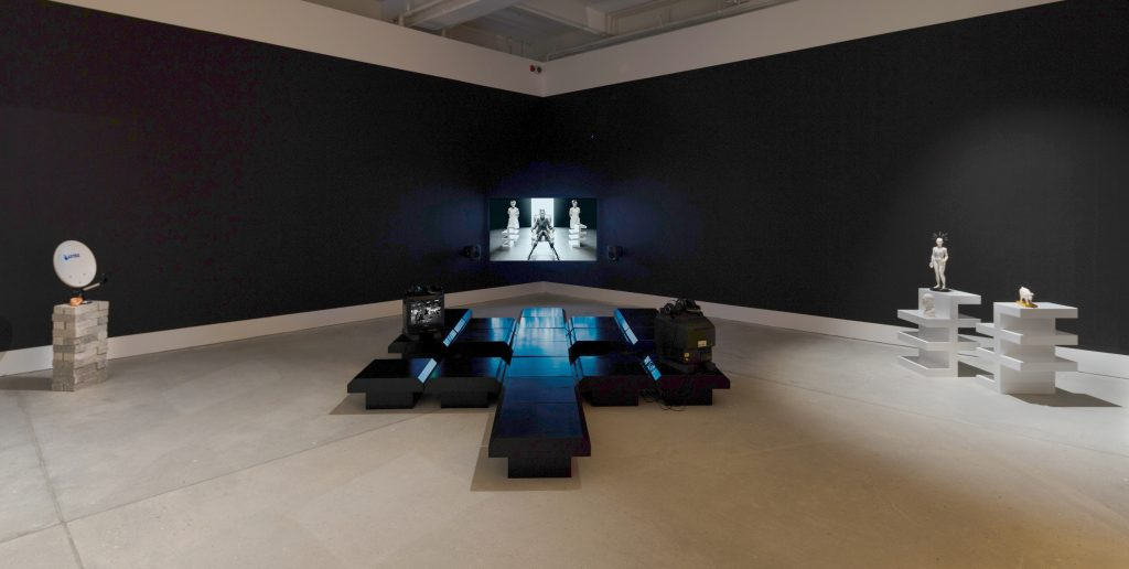 Installation view of Cosmic Call with a flatscreena and two cube monitors. The seats are designed based on a code from the Dutil-Dumas Message