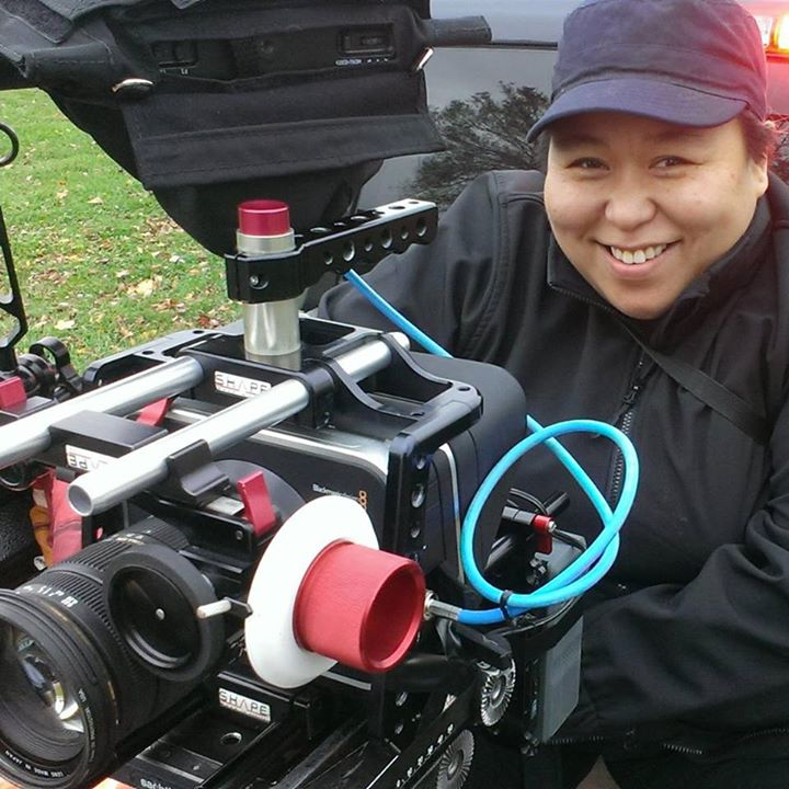 Photo of the artist holding smiling behind an industry film camera.