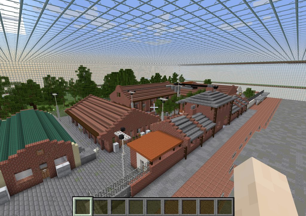 Screenshot of the virtual site of Cattle Depot in Minecraft. Buildings in digital red brick showing the Cattle Depot, with grey roof tiles and trees in the courtyard at the centre.  Behind the Cattle Depot is a small park with trees. And to the left of Cattle Depot is another red brick building with a dark green roof. Buildings a re a mixture of one and two storeys in height. A grid structure was built in the sky above the site by the previous resident artist. This forms a matrix against the blue sky.