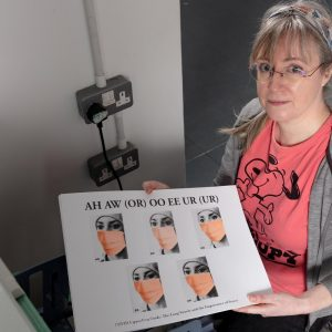 Damien Robinson, a white woman in a pink t-shirt, holding a black and orange Risograph print.