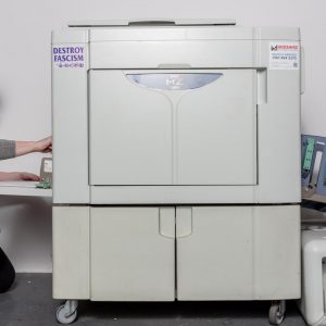 Damien Robinson, a white woman in a pink t-shirt, loading paper in a risograph machine.