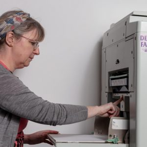 Damien Robinson, a white woman in a pink t-shirt, adjusting the paper feed in a risograph machine.