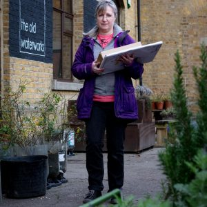 Damien Robinson, a white woman in a purple coat carrying her prints in the garden at The Old Waterworks.