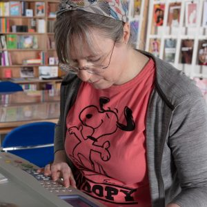 Damien Robinson, a white woman in a pink t-shirt, using a risograph machine at The Old Waterworks print space.