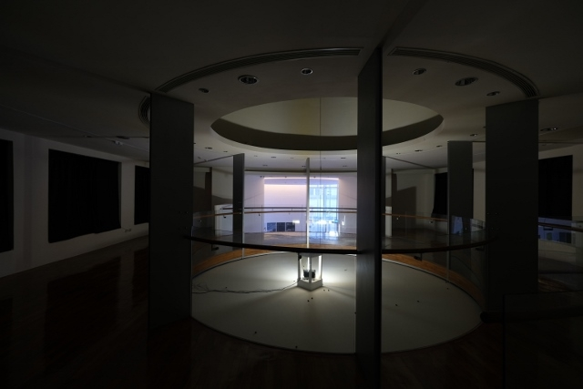 A Installation shot of Hypothesis Atlas and Voyager at the second floor. It's dark circular space with rotating light in the middle.