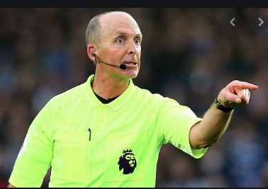 A front facing photo of a football from the waist up, wearing a neon tshirt with a small black lion logo, he has a Britney or call centre style microphone attached to his face, he is balding with some grey short hair around the edge. His face is tensed and wide eyed and his left arm is outstretched as he angrily points at something or someone not visible in the picture. In the background is a very soft focus football crowd.