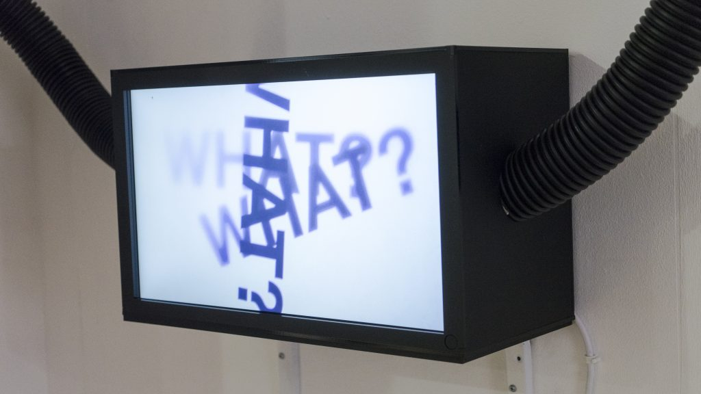 A black rectangular lightbox with a white screen has the word what with a question mark written 3 times on it, black pipes leave the box on the left and right sides.