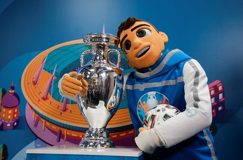 A mascot which has been made to look like a human with short brown hair wearing a blue and white Euros hoody, in a staged photo opportunity situation in a studio, hugging the Euros trophy with their right arm and holding a football in their left. Behind them is a blue background with a graphic design of the stadium on it.