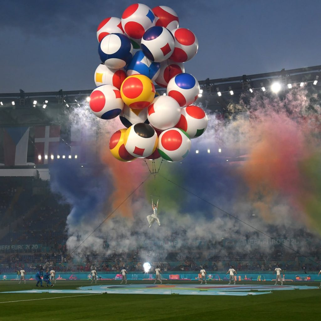 It's a football stadium, the stall are half full in the background. On the pitch are eight dancers in grey jogers and white tshirts, all stood in a power stance two meters apart from each other, above them floats a large cloud of smoke in red, yellow, green and blue. Poised amongst the smoke is an aerial dancers being raised by a large collection of spherical balls decorated with the patterns and colours of Euro flags, they are being assisted by two people wearing blue holding onto ropes from the ground on the left.