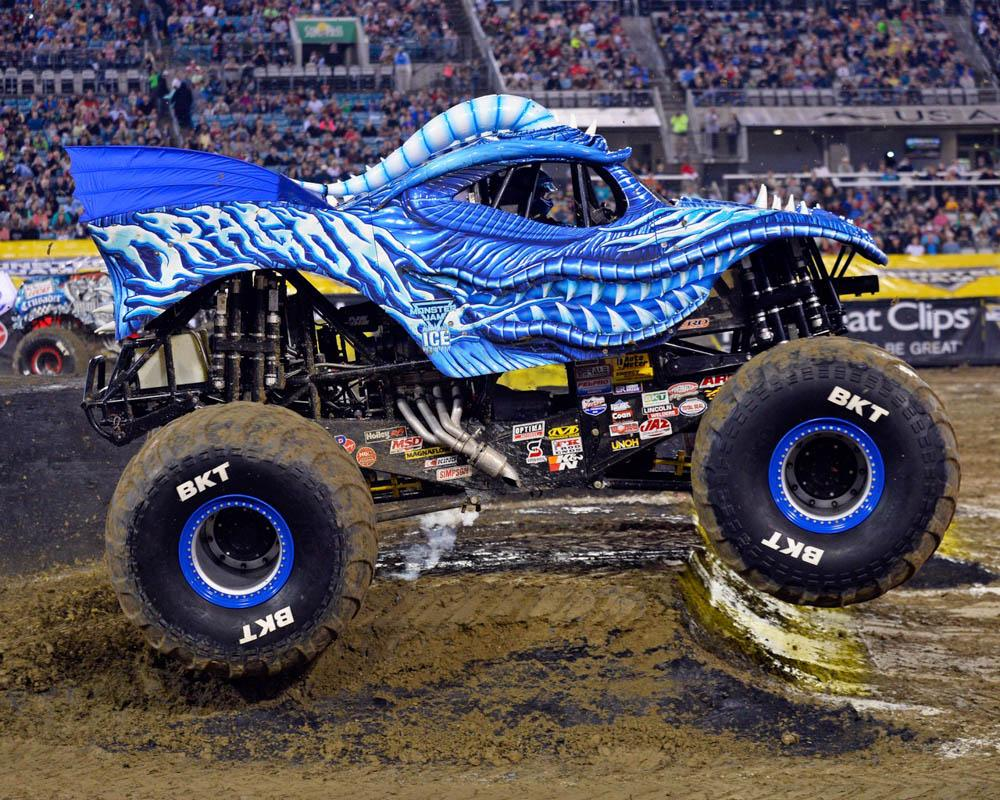 Dragon Ice monster truck, a compact monster truck with a blue dragon body design with scales and teeth and spikes and big wheels. There are colourful logo stickers on the black undercarriage. It is doing a small jump over a very muddy ramp in a stadium filled with people in the background.