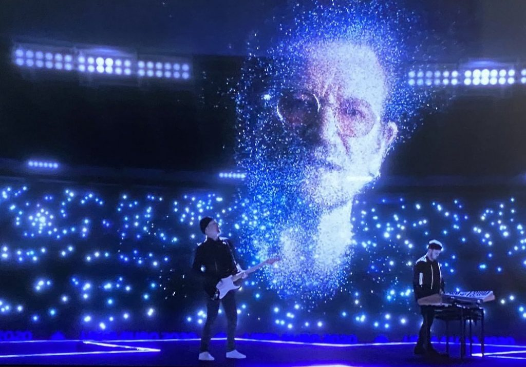 a virtual performance at the opening of the Euros football league. Performed in a black virtual stadium filled with blue twinkly lights, on a stage are two real human performers, one is a man holding a guitar wearing all black on the left and on the right a man wearing all black playing a piano. Floating above them is the large blue cgi head of Bono, the lead singer of the band u2, he is wearing glasses and his head is made up of small dotty drifting blue and white lights
