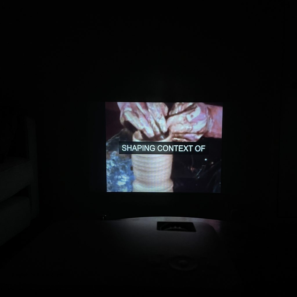 """A picture of a projection on a wall. The picture is very dark as it was taken in a room without lights on. A pair of hands are shaping clay into round cylinder shape. There is a white subtitle against black background in the centre of the image that reads """"SHAPING CONTEXT OF"""" Just below the projected image, there is a hint of the shape of the projector itself."""