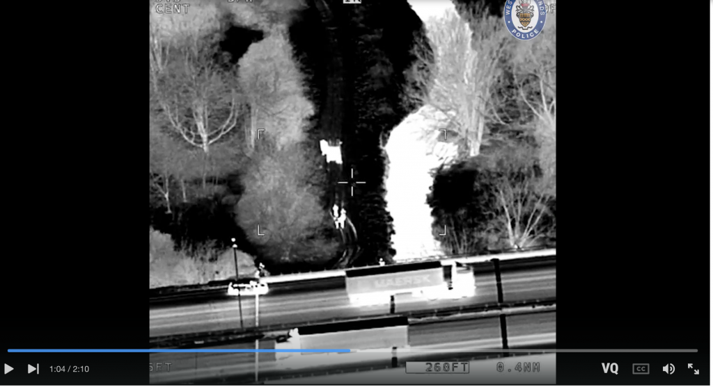 screen shot of black and white night vision/negative image of a motorway over the river cole. a police logo is stamped o the video