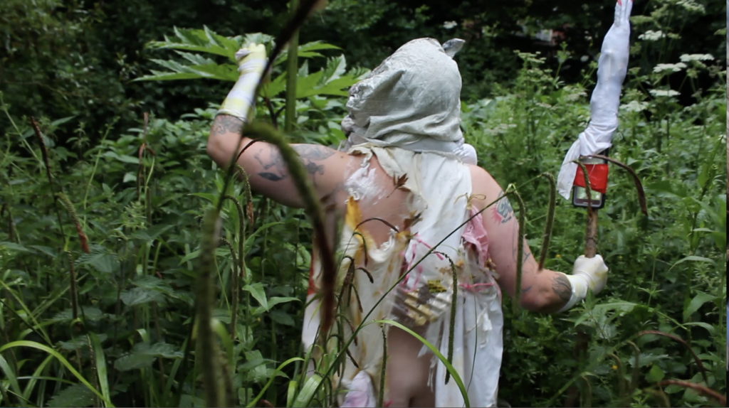white tattooed body + dense green Summer nettle forest + cell phpone taped to stick + rags, pink plastic and skin and string; butt