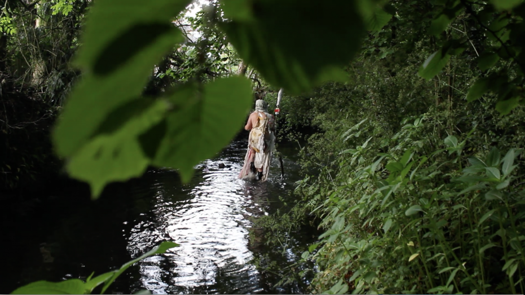 big blurred leaf and green plants and a body in the river, in rags