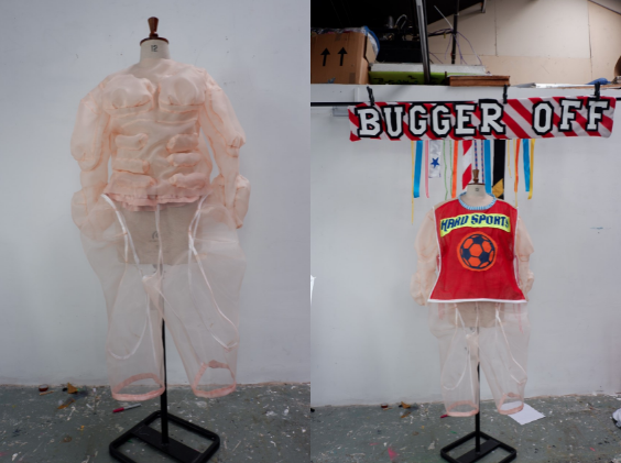 """A split-screen image of two headless torso mannequins adorned with fleshy mesh-like skin. The left mannequin has the same perspective as a changing room mirror and bulging muscles made of fabric. The right mannequin is posing for its birthday snap beneath a striped red and white banner that says """"bugger off"""" in all caps. Multicoloured tassels hang from the centre of the banner and the mannequin is wearing a red bib that has a neon orange football with hard sports written above."""