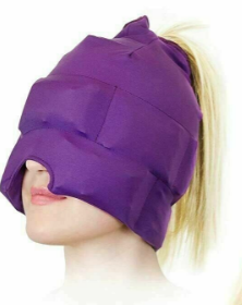 A person with a purple padded hat or cap that covers the entire head and comes down over the eyes and to the end of the nose. They are smiling with their head tilted upwards with blonde straight hair sticking out the top of the cap.
