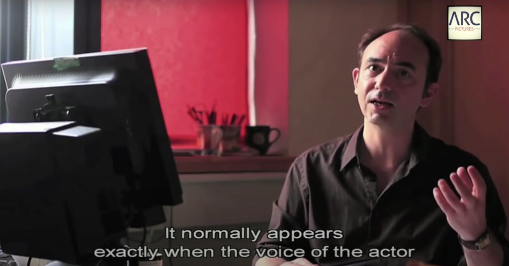 """Screen capture from Youtube The Invisible Subtitler - a person is sitting in the right, wearing a dark coloured shirt. The white subtitle at the bottom says """"It normally appears exactly when the voice of the actor"""". On left there's a black computer screen monitor facing the person, showing only backside of it. The background has red tone, coming from red coloured blind in the window. At the bottom of window, there is 2 cups of utensils and a empty mug cup."""