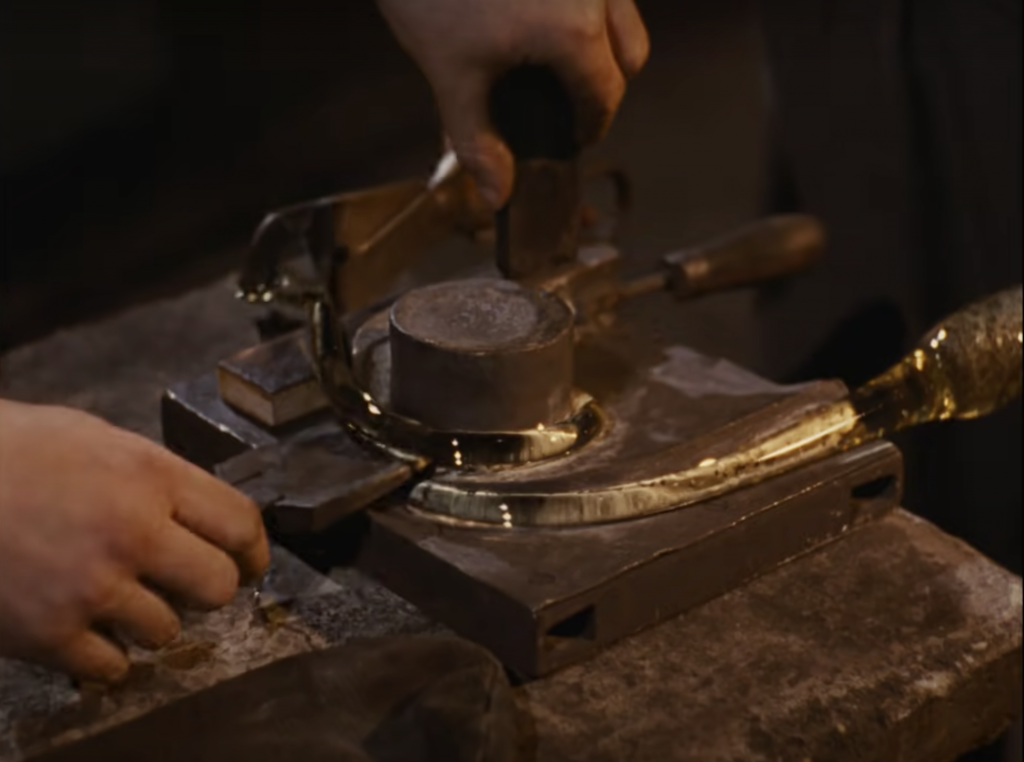 A pair of hands shaping the clear glass with tools around the cylinder shaped metal object on metal work surface.