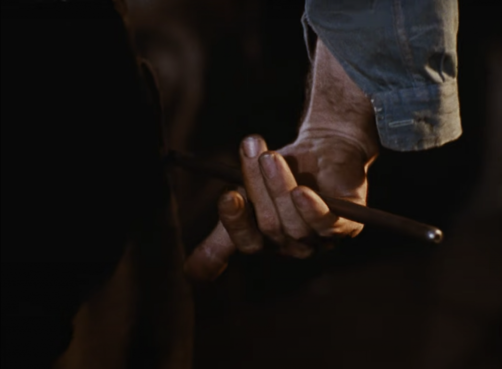 A hand is gently holding the end of brown pole for glassmaking in the centre. The arm is showing arm hair with part of unrolled green shirt sleeve showing.