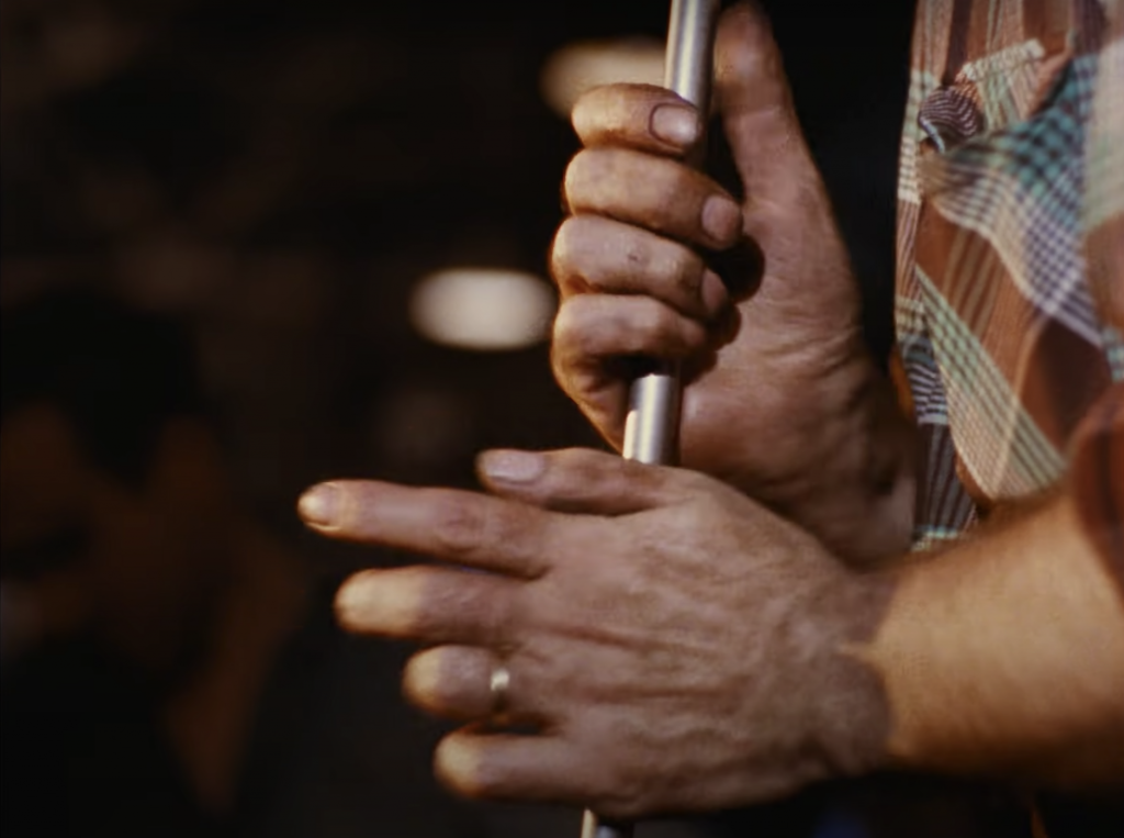 A pair of hands holding metal pole, there is a ring on right hand's ring finger. A person is wearing an orange checkered shirt that is only partly visible.
