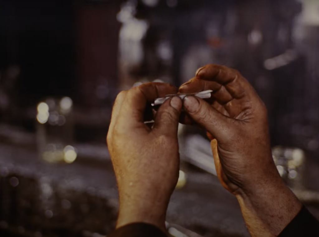 A pair of hands rolling the cigarette. The background is a blurred image of glass making factory scene with empty glass bottles.