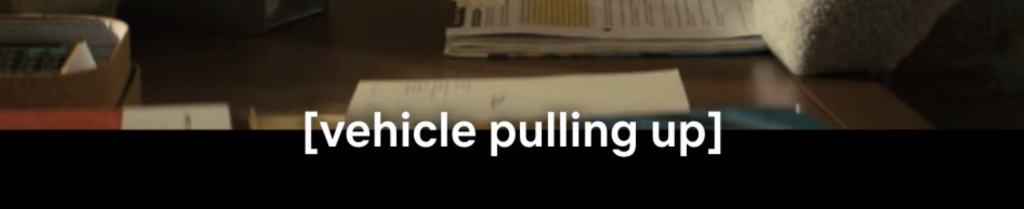 Cropped image of film only showing the subtitle that says [Vehicle pulling up]. Behind the subtitle you can see cropped image of wooden table with paper stacks on it.