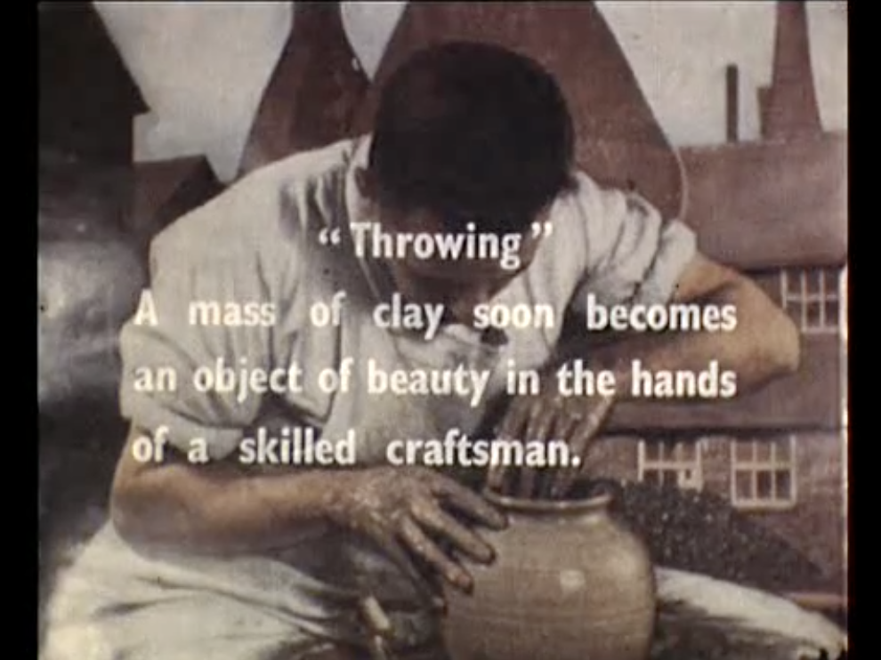 """Scene from Sam Hanna's film """"Village Potter""""- the person who is wearing white shirt and white apron is throwing a round shape of pottery. There is description of what """"Throwing"""" means - """"A mass of clay soon becomes an object of beauty in the hands of a skilled craftsman"""" in simple white font located in centre of image. Behind the person, there is an image of a brown house with small white framed windows and pointed roof."""