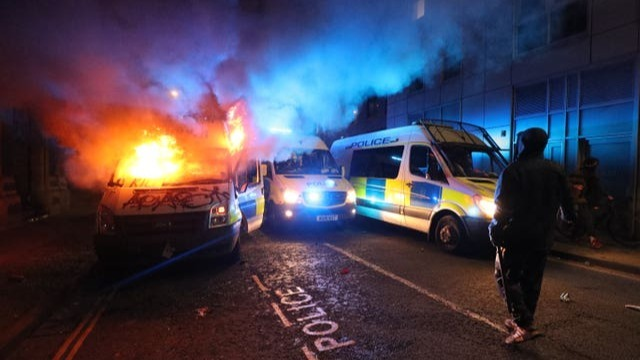 three British police vans parked in a narrow street at night. They are parked at angles and not in a straight line. The left van is on fire which is bursting out of the front window and sides. The bonnet is covered in graffiti which says 'kill' and 'ACAB'. Smoke is billowing and filling the top part of the image, it is glowing orange and red from the fire and blue from the van's lights. The vans in the middle and on the right are not on fire. Their headlights and blue emergency lights are on. A silhouette figure of a person is visible in the foreground on the right from behind.