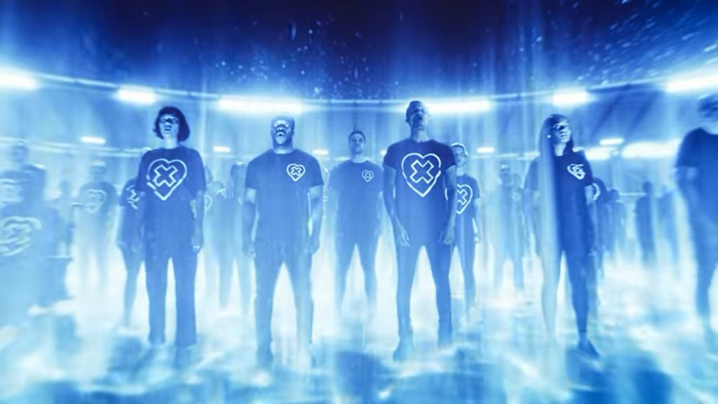 another blue cgi image of a large group of people stood in rows in the stadium, their are bright stadium lights shining around them, they are all wearing black trousers and baggy tshirts that have a symbol on them of a heart with a cross inside. They looks like some kind of cult.