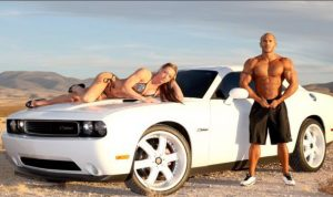 A large white expensive car stands in what looks like a slightly mountainous desert. On the bonnet lies someone in a bikini and heels with an expressionless face