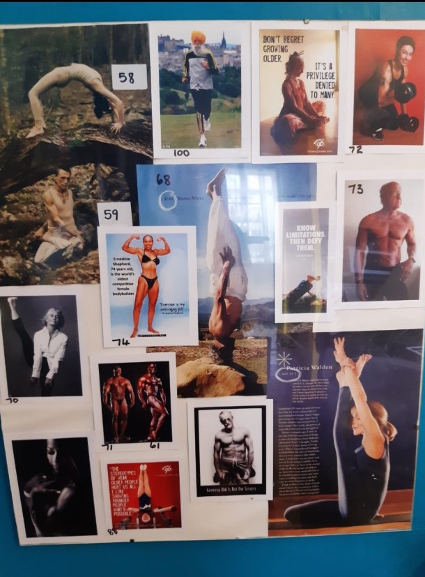 A mood board of many rectangular images that have either been cut from magazines or printed at home on a computer, arranged and put inside a clip frame. They include muscly older people doing a variety of fitness activities including yoga, body building, swimming and running. Many of them are posed with little clothing on to present their physique. The images have been marked with numbers in a black felt pen, these are the ages of the people shown in the pictures which range from 58 to 100 years old. Some of the images contain text, inspirational quotes from the people in the pictures and information about them, which is mostly not big or clear enough to read. Some quotes that are visible say, 'Don't regret growing older. It's a privilege denied to many' and 'Know Limitations. Then Defy Them.'
